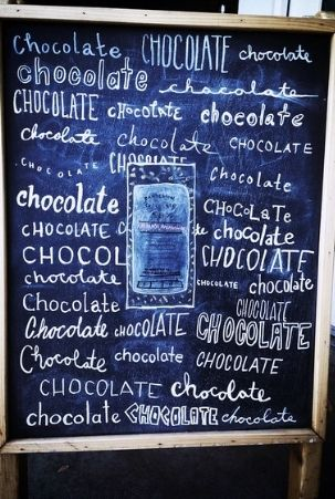 Chalkboard sign celebrating chocolate at Dandelion Chocolate Factory in San Francisco's Mission District.